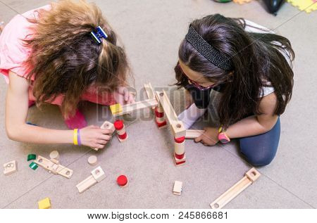 High-angle view of two pre-school girls sharing wooden toy blocks while building together a challenging structure on the floor at the kindergarten