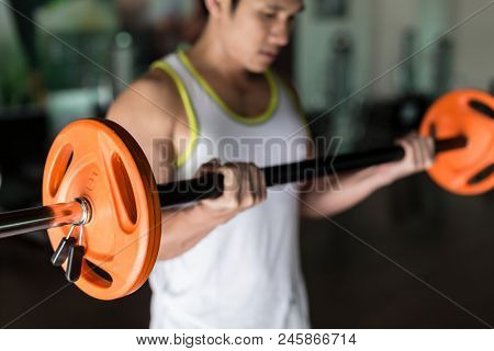 Determined young man holding a barbell with supinated grip while exercising bicep curls from standing position at the gym poster