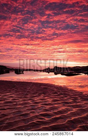 Sunrise Reflecting In A Pool Of Water At An Australian Beach Alongside The Iconic Great Ocean Road