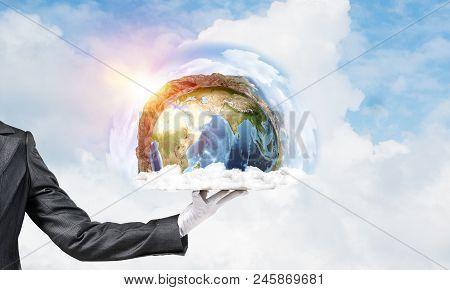 Hand Of Waitress Presenting Earth Globe On Tray.