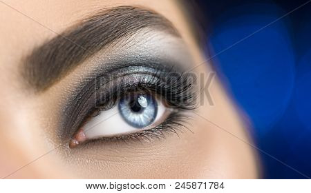 Beauty Brunette Woman blue Eye with Perfect Makeup. Beautiful Professional smokey eyes holiday Make-up. Perfect eyebrows shaping, eyes and eyelashes. Skin care. Beauty Girl's Face evening make up