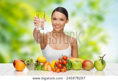 diet, healthy eating and people concept - woman with food on table drinking water over green natural background