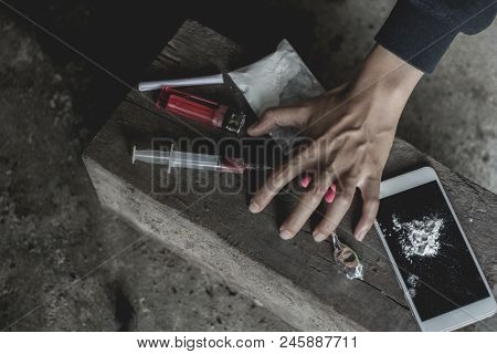 Young Human Hand Trying To Reach Drugs, The Concept Of Crime And Drug Addiction. 26 June, Internatio