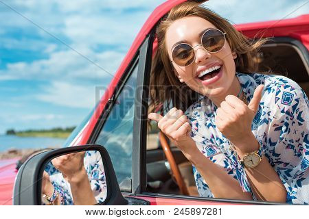 Excited Young Woman In Sunglasses Sitting In Car And Showing Thumbs Up During Trip