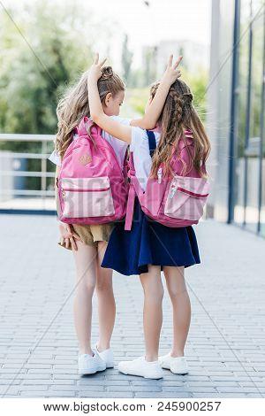 rear view of little schoolgirls making horns joke gesture to each other on street poster