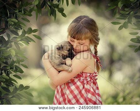 Little Girl With Little Cute Girl With Closed Eyes Gently Hugs A Little Puppya Puppy