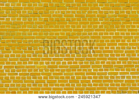 Close-up of a colorful Yellow Brick Wall. View to a Yellow Wall made of Brick Stones. Natural Textures and Backgrounds.