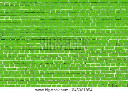 Close-up of a colorful Green big Brick Wall.  View to a Green Stone Wall made of Bricks.  Natural Textures and Backgrounds.