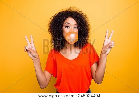 Portrait Of Cheerful Cool Girl With Modern Hairdo Blowing Chewing Bubble Gum Gesturing V-signs With