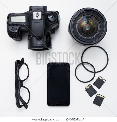 Photographer's Equipment - Top View Of Camera, Lenses, Cards And Smart Phone Over White Table