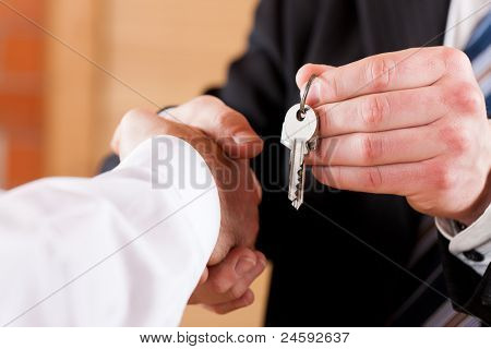 Two businessperson shaking hands; only hands to be seen and a key is be given