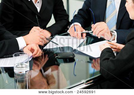 Business - Besprechung in einem Büro; Juristen und Anwälte (nur Hände) diskutieren, ein Dokument oder einen Vertrag