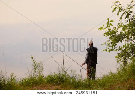 The Fisherman Catches On The Lake At Dawn