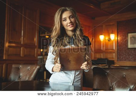 Beautiful Waitress In A Luxury Restaurant Offers A Menu