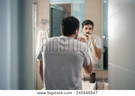 Hispanic Person With Beard Grooming In Bathroom At Home For Morning Routine And Body Care. White Met