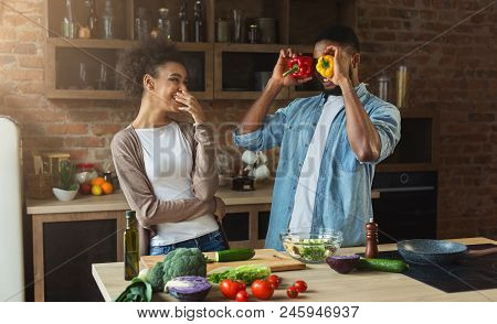 Happy African-american Couple Cooking Healthy Food And Having Fun Together In Loft Kitchen
