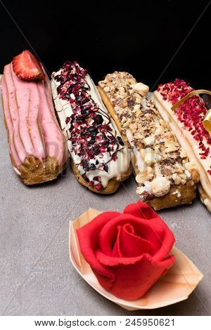 Sweet Delicious Colorful French Eclairs. Group Of French Dessert With Marzipan Red Rose. Eclair Back