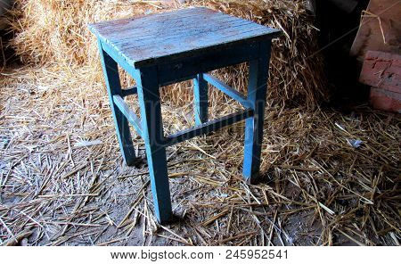 Old Wooden Stool In Blue Color Stands On The Floor In Barn With Straw