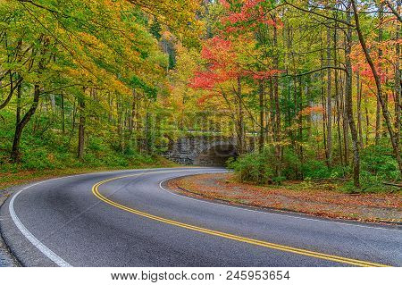 A Curving Smoky Mountain Road Going Toward A Stone Tunnel In Autumn.