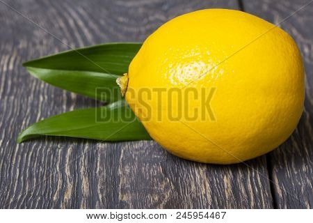 Large Bright Yellow Lemon With Leaves Lies On Grey Wooden Surface