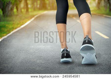 Sports Background, Runner Feet Running On Road Closeup On Shoe, Sport Woman Running On Road At Sunri