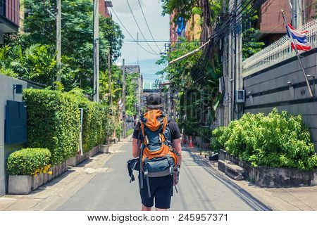 Man With Backpack Walking In The Streets Of Bangkok. Backpacker In Travel
