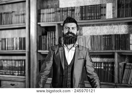 Bookshelf And Library Concept. Bearded Man Standing Near Bookshelf And Smiling.