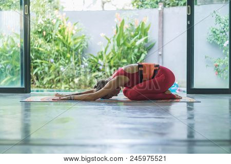 Side View Of Young Woman Practicing Yoga In Extended Child Utthita Balasana Pose