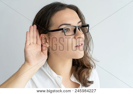 Focused Curious Office Girl In Glasses Eavesdropping. Young Caucasian Woman Keeping Hand At Ear And