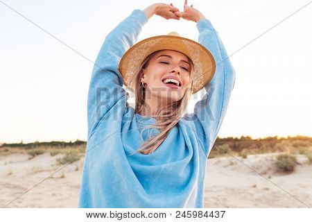 Photo of pretty smiling young emotional caucasian lady looking aside on the beach.