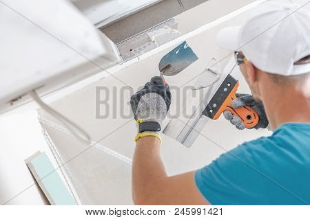 Building Drywall Ceiling Elements For Led Lighting. Caucasian Worker Patching Drywall.