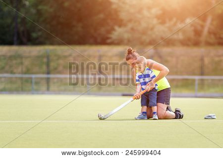 Small Boy Training Playing Field Hockey With Stick On The Field With His Mother