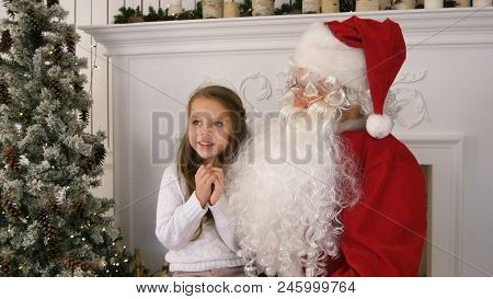 Undecided Little Girl On Santa Claus Lap Thinking About Her