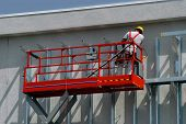 Constuction worker works on high scaffolding at a construction site. The lift has a red scaffoling at the end of a boom. One worker is hard at work. poster