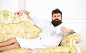 Man on thoughtful face in bathrobe drink coffee in luxury hotel in morning, white background. Luxury life concept. Man with beard and mustache enjoy morning while sitting on old fashioned luxury sofa. poster