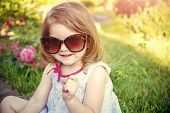 Innocence, purity and youth. Girl in sunglasses sitting in park on floral environment. Child smiling with raised finger in summer garden. Summer vacation and lifestyle. Future and flourishing. poster