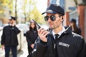 Portrait Of A Male Security Guard Talking On Walkie Talkie poster