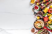Assortment various barbecue food grill meat, bbq party fest - shish kebab, sausages, grilled meat fillet, fresh vegetables, sauces, spices, white marble background, above copy space poster