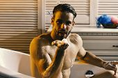 Man with beard and charming face blowing foam from palm. Guy in bathroom covered with foam with toiletries on background. Sex and erotica concept. Macho sitting naked in bathtub, selective focus. poster