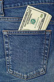 Pocket Money. New Dollar Roll In Hip Pocket Of Worn Blue Jeans Close-up