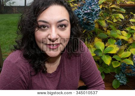 middle aged woman in her 40s sitting outside in fall poster