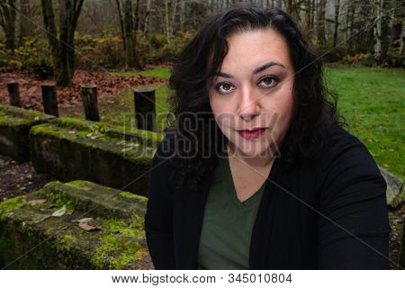 Middle Aged Woman In Her 40s Sitting Outside In Fall