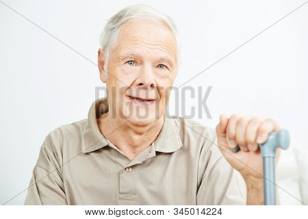 Old smiling man with crutch stick sits contentedly in the retirement home