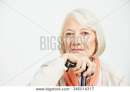 Old woman with crutch stick looks sadly into the camera