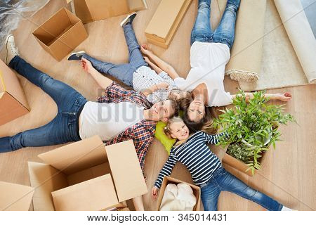 Family moving to their new home The home is lying happily between moving boxes on the floor