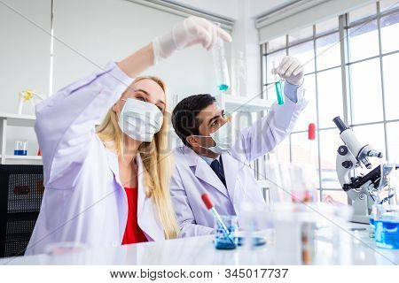 Two Scientists Are Working Holding Looking At Test Tube With Sample In A Chemistry Lab Scientist Or