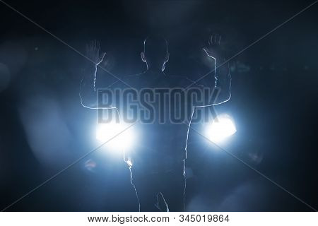 a silhouette of a male criminal suspect with hands up during night pursuit in front of the police car headlights poster