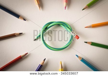 Colored Pencils With One Flexible Pencil On White Background. The Concept Of Flexibility In Decision