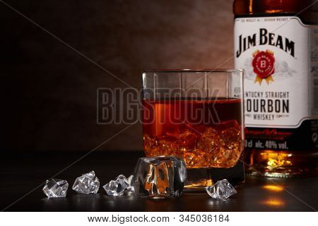 St.Petersburg, Russia - December 2019 - Bottle of Jim Beam bourbon whiskey and glass with drink and ice  on wooden table on brown background with copy space. Kentucky straight bourbon whiskey