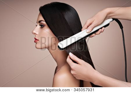 Hairdresser Straightening Long Dark Hair With Hair Irons. Beautiful Woman With Long Straight Hair. S